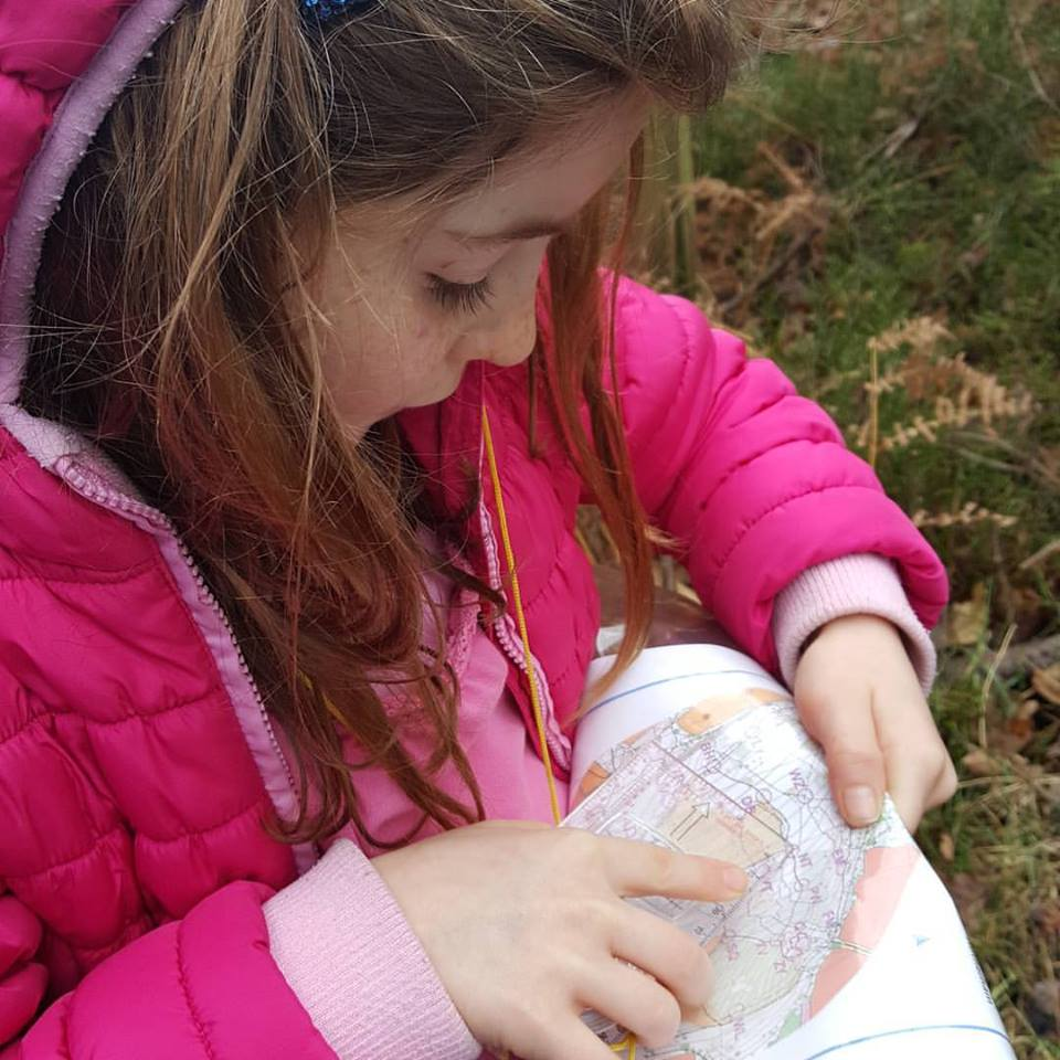 image showing a girl map reading for orienteering