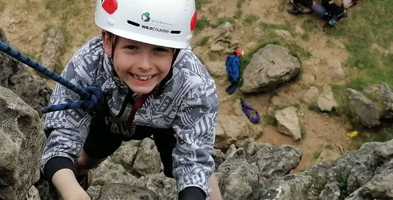boy finishing a rock climb at Harborough Rocks in the Peak District